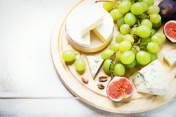 various types of cheese with figs and grapes
