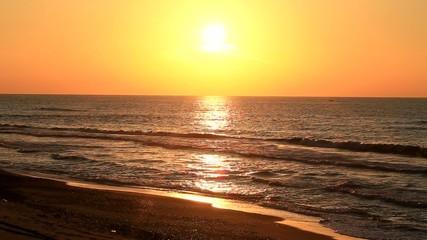 砂浜と夕日と漁船