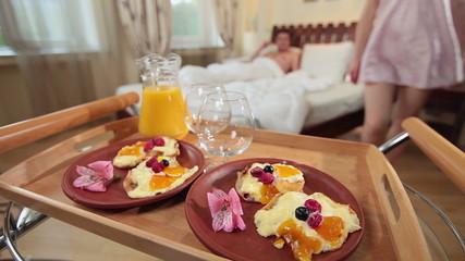 Sexy girl in nightdress brings boyfriend breakfast in bed