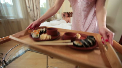 Wife bringing tray with Japanese sushi to husband in bed