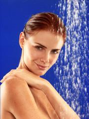 Mujer pelirroja bajo la ducha.