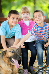 little girl and boys in the park with a German Shepherd