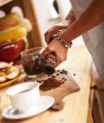Senior woman making ground coffee in her kitchen