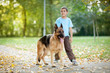 happy child with a German Shepherd Dog in the park