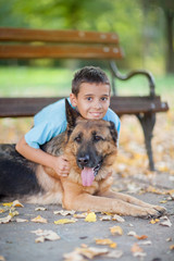 child with a German Shepherd Dog in the park