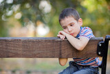 orphan, unhappy boy sitting on a park bench and crying