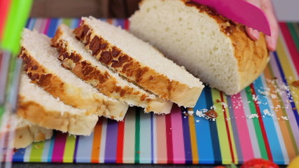 Close up slicing bread in colorful contemporary kitchen