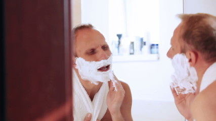 Funny man signing during shaving in the morning