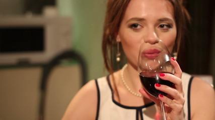 Beautiful girl clinking wineglasses with boyfriend in restaurant