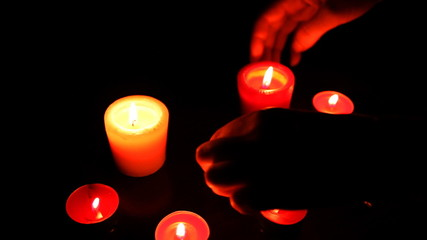 female hands moved red candles with lights in dark, closeup