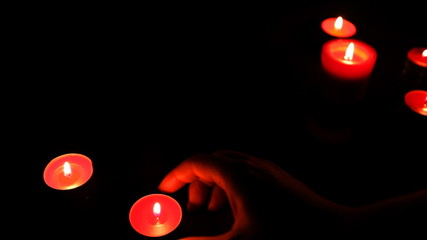 female hands put red candles with wax in semicircle, small light
