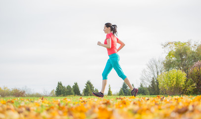 Young brunette woman running in park.