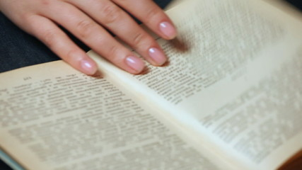 female hand shatters pages of old book with pictures closeup