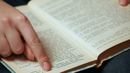 female hand shatters pages and show text of old book closeup