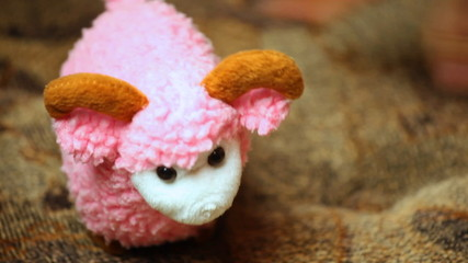 woman's hand playing toy pink sheep on couch closeup