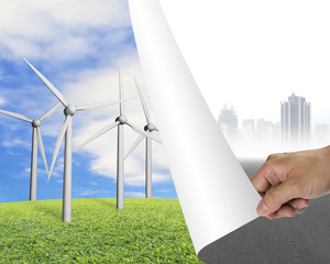 Hand turning gray cityscape page revealing group of wind turbine