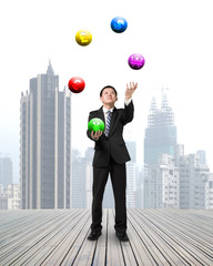 businessman throwing and catching currency symbol balls