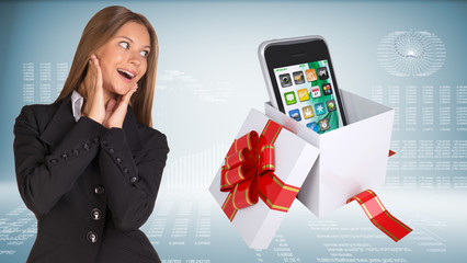 Cheerful businesswoman and open gift boxe with smart phone