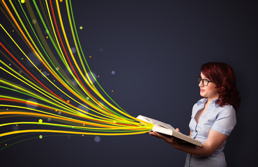 Pretty young woman reading a book while colorful lines are comin