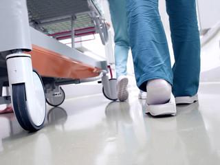 Medical staff moving patient through hospital corridor