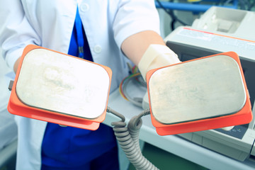 Plates defibrillator in the hands of the doctor is ready to save