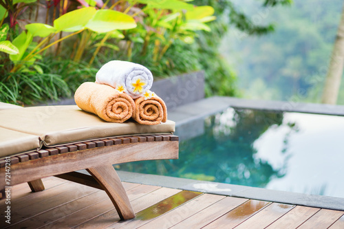 Towels with white frangipani flowers in spa - 72147281