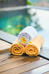 Towels with white frangipani flowers in spa