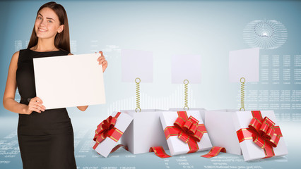 Businesswoman holding empty paper. Open gift boxes with blank