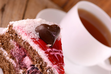 Piece of cake with chocolate heart on wooden background