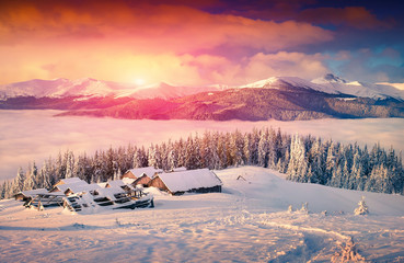 Colorful winter sunrise in the foggy mountains