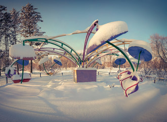 A snow-covered roundabout in the city park. Retro style.