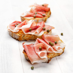 Grilled country bread with ham and capers