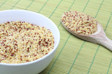 Bulgur in white bowl and wooden spoon