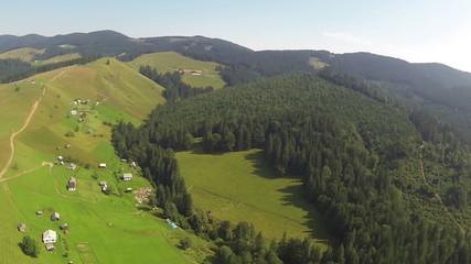 Flight over  small mountains with wood and village.  panorama