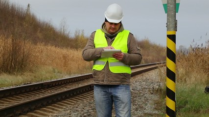 Engineer with tablet PC near the railway