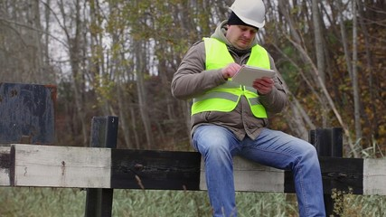 Worker with tablet PC sitting on the defence barrier
