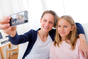 Attractive woman and little sister taking selfie