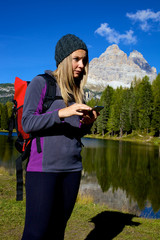 Happy hiker looking for road map on smart phone in the mountain