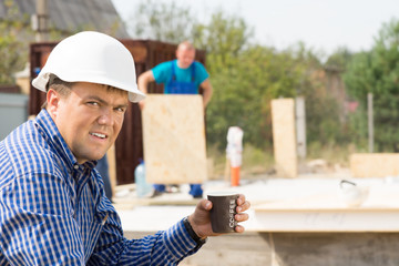 Male Engineer Holding Cup of Coffee at Site