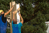 Two builders erecting wall panels on a new house poster