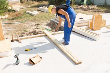 Workman applying glue to an insulated beam