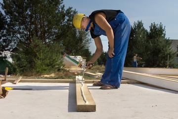 Builder applying glue to a wood beam