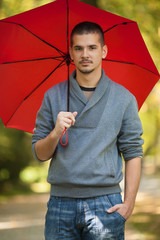 Portrait of a young man holding a red umbrella