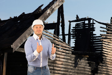 Engineer in Thumbs Up Sign in Front Damaged House