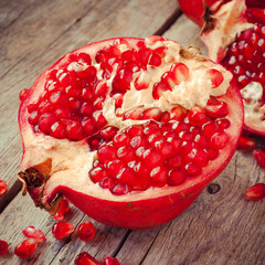 Piece of ripe pomegranate and red grains on wooden  table