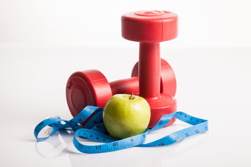 Red dumbbells weight with measuring tape and green apple