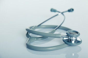 Gray stethoscope on white glossy table