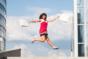 Happy girl with shopping bags jumping