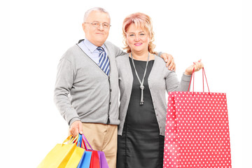 Mature couple posing with shopping bags