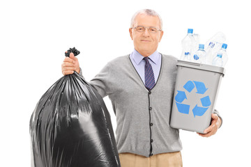 Senior holding a recycle bin and a garbage bag